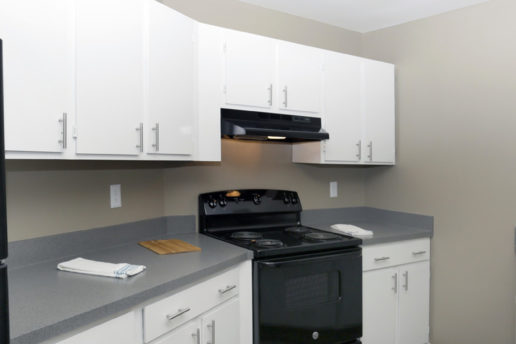 Kitchen with white cabinets, gray countertops, and black appliances