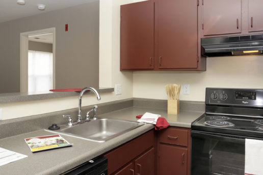 Kitchen with brown cabinets, gray countertops, and black appliances, stainless steel sink
